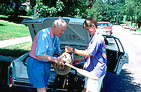Grandfather and grandson age 80 and 13 packing car for family trip.  St Paul Minnesota USA