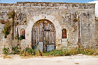 Botrugno (LE) - Salento - Una masseria diroccata ha mantenuto intatto il portone d'ingresso. Ai lati quel che resta di due icone sacre di cui si notano ancora i colori sbiaditi della pittura.