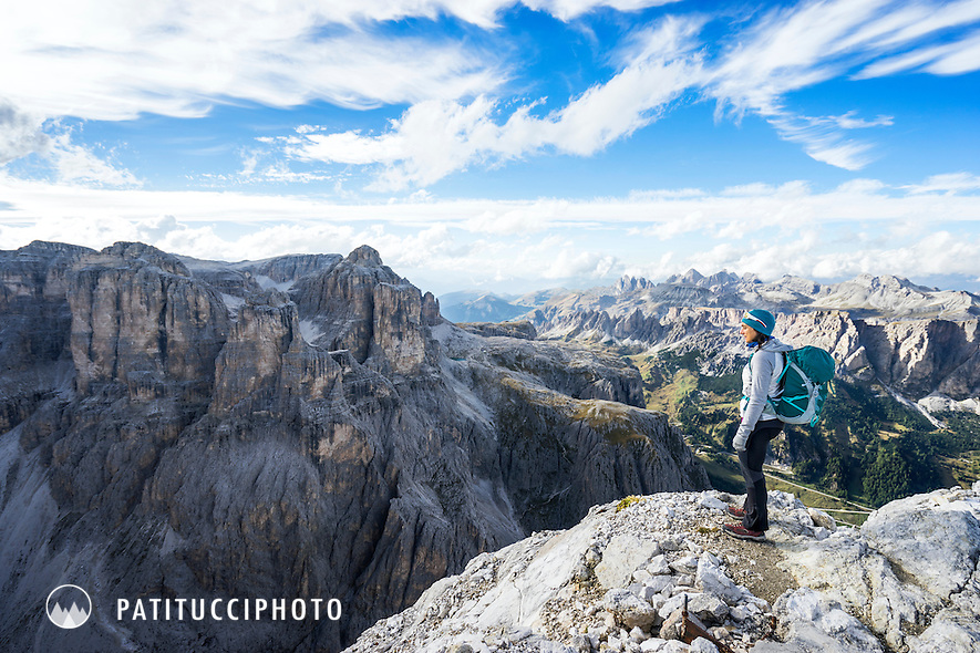 A woman hiker stands in the Italian Dolomites Sella Massif looking out at the landscape
