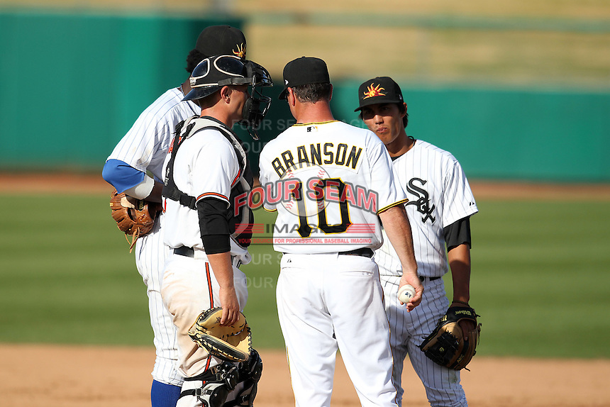Mesa Solar Sox coach Jeff Branson #10 talks to (L-R) third baseman Junior Lake, catcher Brian Ward, and Taylor Saldino during an Arizona Fall League game against the Phoenix Desert Dogs at HoHoKam Park on November 3, 2011 in Mesa, Arizona.  Mesa defeated Phoenix 8-7.  (Mike Janes/Four Seam Images)
