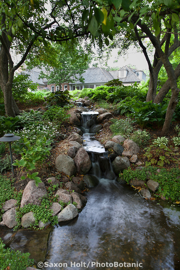 Waterfall to pond with stream edged with stone through naturalistic shady backyard garden