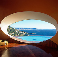A view from an oval window in the main reception room across the infinity pool to the Mediterranean beyond