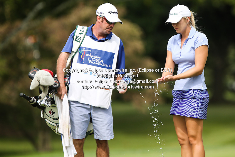 Jennifer Kirby (right) washes her hands on the 10th fairway with her caddie at the LPGA Championship 2014 Sponsored By Wegmans at Monroe Golf Club in Pittsford, New York on August 16, 2014