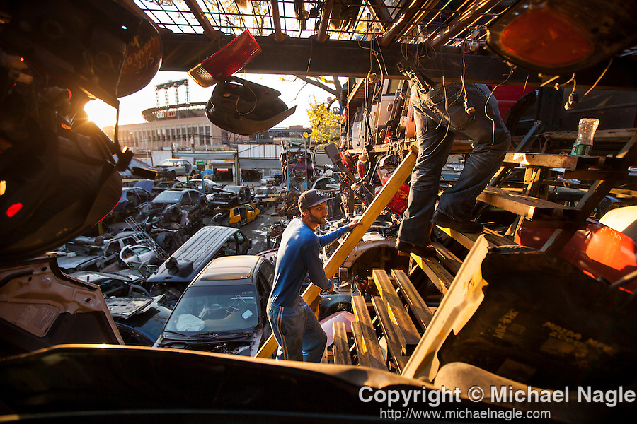 QUEENS, NY -- OCTOBER 22, 2013:  Yoni, center, and Barry, right, owners of ACDC Scrap Metal Inc., climb to the top of their storage in Willets Point on October 22, 2013 in Queens.  Photographer: Michael Nagle for The New York Times