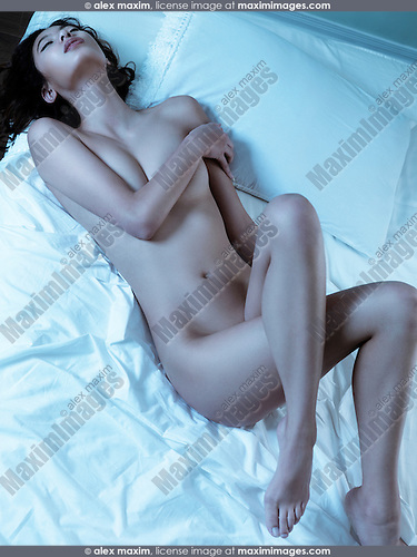 Beautiful sexy young nude woman lying in bed on white sheets lit with blue light