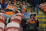 A fan reading a matchday programme in the stands at Blackpool Football Club's Bloomfield Road stadium before the club played host to Liverpool FC in a Premier League match. The home side won by two goals to one. It was the first time the clubs had met in a league match since Blackpool were last in the top division of English football in 1970-71.