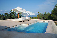 The outdoor lap pool is situated at one end of a series of terraces to the rear of this holiday home on the island of Ibiza
