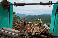 Nepal, Gorkha District, Ramele, Gorkha. Family cleaning up their house damaged by the earthquake.