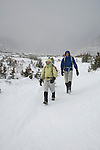 Couple (MR) of hikers dressed for the cold and wind, and prepared with mountaineering gear, in the krummholz near treeline, winter, Rocky Mountain National Park; blowing snow, February 2008, Colorado, USA, Rocky Mountains