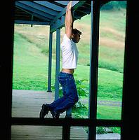 Man hanging from porch beam seen through screen door<br />