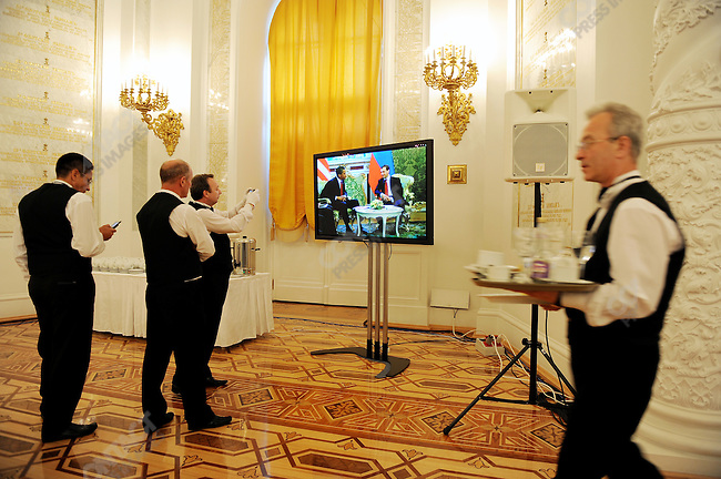 Waiters in the Georgiyevsky Hall in the Kremlin photographed President Obama as live translation of his meeting with President Medvedev in another part of the Kremlin came onto the screen. Moscow, Russia. July 6, 2009