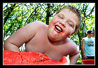 Tobin Griggs, 11, laughs while competing in a watermelon eating contest during a summer day-camp held at the City of Temple Recreation Center in Temple, TX on June 24, 2005.  Griggs finished second in the competition. (Brian Ray for the Temple Daily Telegram)