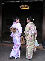 Japanese women in traditional kimonos visit a Kyoto temple