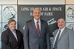 Garden City, New York, USA. June 21, 2018. L-R, DEBORAH HENLEY, VP Executive Editor of Newsday, representing inductee aviator and Newsday founder Alicia Patterson; Inductee former NASA astronaut MIKE MASSIMINO; and LOUIS MANCUSO JR, representing his parents, inductees Louis and Carol Mancuso, pose at Long Island Air & Space Hall of Fame Wall at Cradle of Aviation Museum during Class of 2018 Induction.