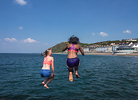 UK Weather: Aberystwyth, Ceredigion, West Wales Thursday 12th May 2016. <br />Two young University students take advantage of the warm weather by 'Bombing' off the jetty into the clear blue sea of Cardigan Bay.
