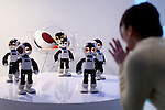 """A woman ask the communication robots called """"Robi"""" to dance during a press preview for """"Robi cafe"""" where visitors can interact with the robots while enjoying meals and drinks in Tokyo, Thursday, January 15, 2015. The robot can be built by assembling parts sent along with a weekly magazine by Deagostini. The cafe will open from January 16 until February 8. (Photo by Yuriko Nakao/AFLO)"""