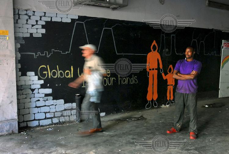 An Israeli man walks by an African man, a kitchen worker in a restaurant who is on break.