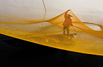A fisherman toils away beneath a large, square yellow net.  Balanced on the edge of his small boat he uses a stick to propel it while looking to see what he has caught.<br /> <br /> The photographs were captured on the shallow waters of the Truong Giang River in Quang Nam Province, Vietnam, where the old man works daily.  SEE OUR COPY FOR DETAILS.<br /> <br /> Please byline: Ngoc Diem/Solent News<br /> <br /> © Ngoc Diem/Solent News & Photo Agency<br /> UK +44 (0) 2380 458800