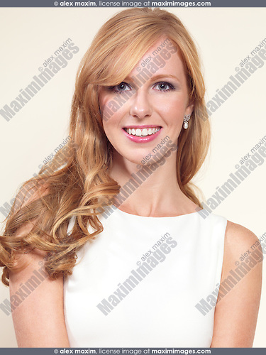 Portrait of a beautiful young smiling woman with long blond hair isolated on light beige background
