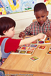 3 year old boy with friend w. friend,girl, age 3, playing w. puzzle together matching memory game girl sharing piece handing it to him vertical