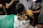 Relatives of Palestinian of Ahmed al-Assi, 21, who died of his wounds endured during clashes with Israeli troops in a tent city protest where Palestinians demand the right to return to their homeland at the Israel-Gaza border, mourn over his body during his funeral, in Khan Younis in the southern Gaza Strip on June 14, 2018. Photo by Ramadan Elagha