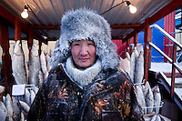 A portrait of a man selling frozen fish at the Yakutsk outdoor fish market. Yakutsk is one of the coldest cities on earth, with winter temperatures averaging -40.9 degrees Celsius.