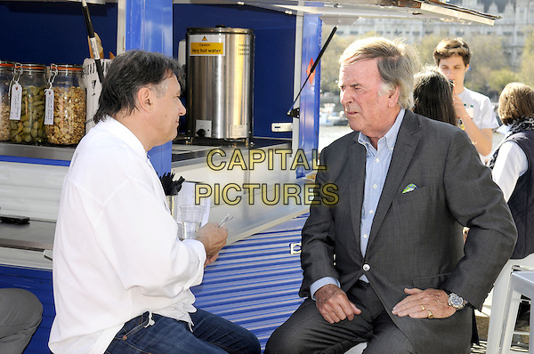 Raymond Blanc & Terry Wogan.being filmed for the BBC at the Real Food Festival, Southbank, London, UK, May 3rd 2013..half length sitting on stool white chef suit jeans  grey gray blue shirt jacket bar .CAP/PP/BK.©Bob Kent/PP/Capital Pictures