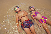 Two young children soaking up the sun at the beach shoreline