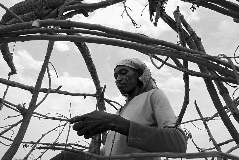 En Geneina, West Darfur, August 8, 2004.A woman builds a makeshift shelter in Ardamata IDP camp, in the outskirts of the city.