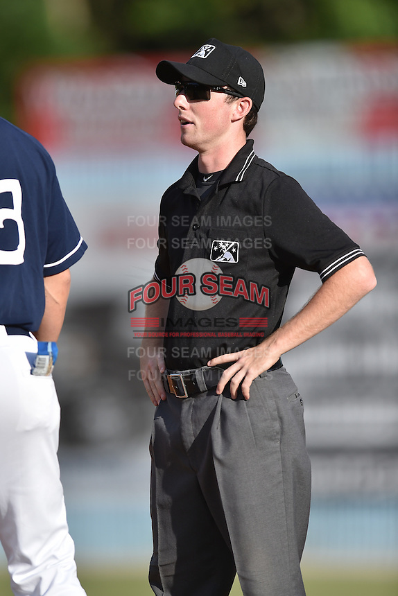 Asheville Tourists manager (13) discusses a play with first base umpire Anthony Perez during a game against the Columbia Fireflies at McCormick Field on June 18, 2016 in Asheville, North Carolina. The Tourists defeated the Fireflies 5-4. (Tony Farlow/Four Seam Images)