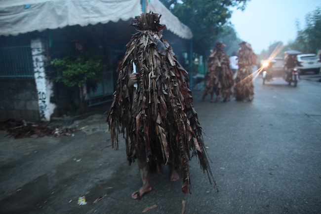 "Participants in the annual Taong Putik, or ""mud people,"" festival walk through the streets, asking alms from passersby, while on their way to a special Mass at the Catholic church in the village of Bibiclat, on Luzon island, Philippines. The festival honors St. John the Baptist, and the mud, banana leaves and vines that devotees wear symbolize the animal skins the saint wore in the Bible. June 24, 2011."