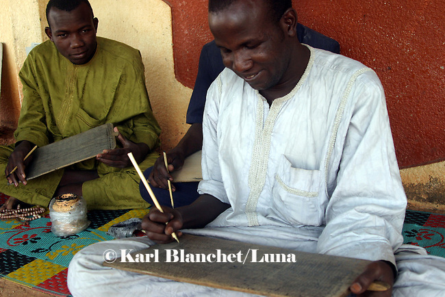 Talibes writing coranic versets on wooden boards outside the house of the marabout in Maradi, Niger. In Niger, coranic schools still exist and are very traditional. Talibe, pupils, even go and beg for money and food in the afternoon in order to pay the marabout.