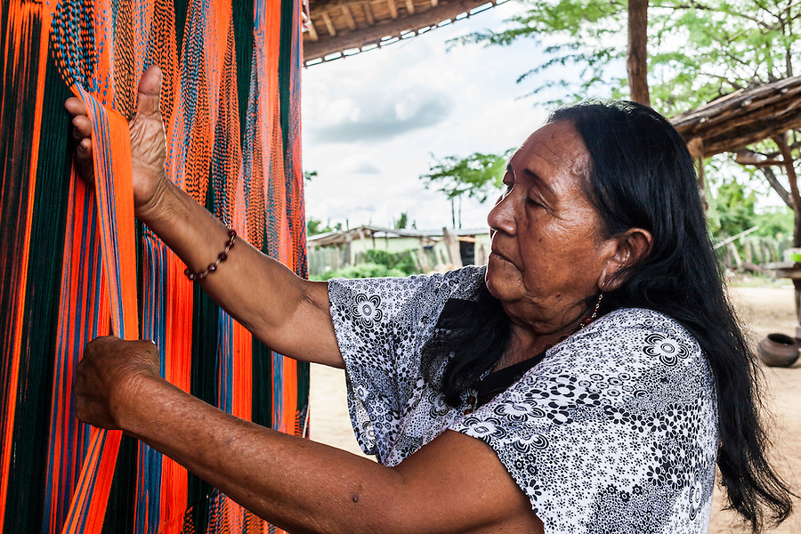 "Elderly Wayuu indigenous woman weaving a ""chinchorro"" or Colombian Hammock.  Knitting, crocheting and weaving are fundamental to the social and economic lives of Wayuu women in La Guajira, Colombia."
