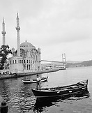 TURKEY, Istanbul, boy standing on boat with Ortakoy Mosque in the background