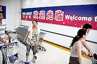 Shoppers get shopping carts before entering Wal-Mart at Wanda Plaza in the central Xinjeikou shopping area of Nanjing, Jiangsu, China.