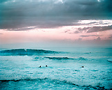 USA, Hawaii, Oahu, a surfer on a large wave at Pipeline at sunrise with the full moon