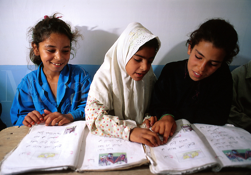Smiling female Iraqi students reading in school. Iraq.