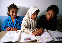 Smiling female Iraqi students reading in school. Iraq.