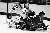 Seals goalie Gary Simmons holds off Kansas City Scouts Robin Burns with help from Jim Neilson  (1975 photo by Ron Riesterer)