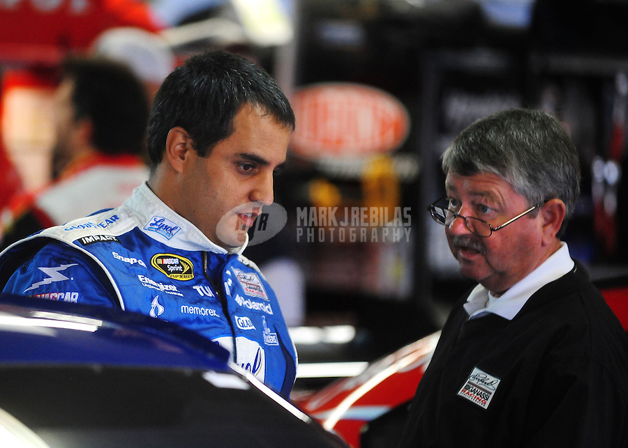 Oct. 15, 2009; Concord, NC, USA; NASCAR Sprint Cup Series driver Juan Pablo Montoya (left) talks with team manager Tony Glover during practice for the Banking 500 at Lowes Motor Speedway. Mandatory Credit: Mark J. Rebilas-