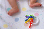 Five month old baby girl in crib sleeping focus on legs and feet with toy keys