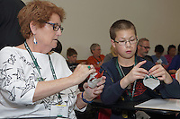 OrigamiUSA 2016 Convention at St. John's University, Queens, New York, USA. Creasers in Paul Frasco's Dragon Hatchling class. Laszlo Harangoza (r) helps Martha Landy (l) New Jersey.