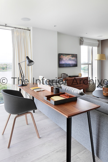 A modern sitting room furnished with two grey sofas and a desk and chair arrangement acts as an informal office area