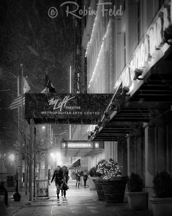 People walking on Main Street by the Loft Theater on snowy night, bw