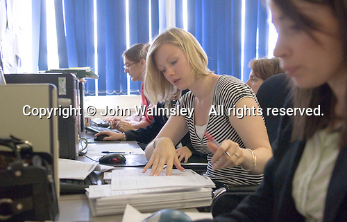 Newly Qualified Maths Teacher marking papers on computer in the Staff Room.