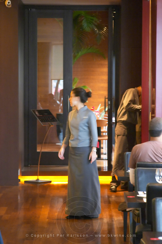 A waitress dressed in long grey skirt and gray blouse. The Restaurant Red at the Hotel Madero Sofitel in Puerto Madero, Buenos Aires Argentina, South America