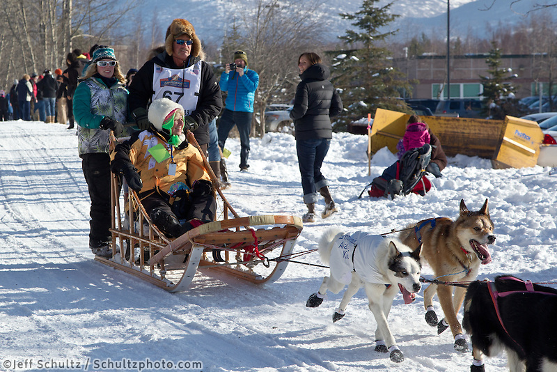 Sonny Lindner and team run past spectators on the bike/ski trail during the Anchorage ceremonial start during the 2013 Iditarod race.    Photo by Britt Coon/IditarodPhotos.com