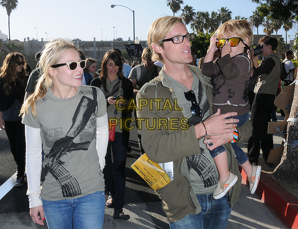 "KRISTEN BELL & JASON RUSSELL .City Hall at The Invisible Children's ""THE RESCUE"" Rally at City Hall in Santa Monica, California, USA, .April 25th 2009..half length green gun print t-shirt white top ray bans wayfarers sunglasses cream two tone jeans child boy kid carrying glasses jacket .CAP/DVS.©DVS/RockinExposures/Capital Pictures"