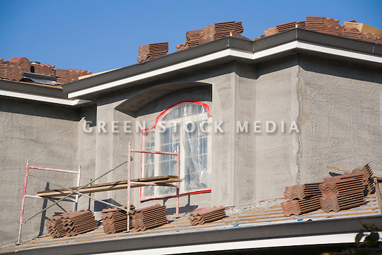 Stacks of red brick roof tiles on a roof of a new single family home under construction. Fresh light grey stucco covers wire mesh on the walls. Cupertino, California, USA