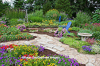 63821-21813 Flower garden with stone paths, blue Adirondack chair, bird bath, obelisk, bird house, and trellis, Homestead Purple Verbena (Verbena canadensis), Red Verbena, New Gold Lantana (Lantana camara), sedums, raspberry blast petunia and diamond frost euphorbia in blue pot, Butterfly Bushes, Joe Pye Weed (Eupatorium purpurea) Moon Vine on trellis, Raspberry Wine Bee Balm (Monarda didyma)  Marion Co., IL